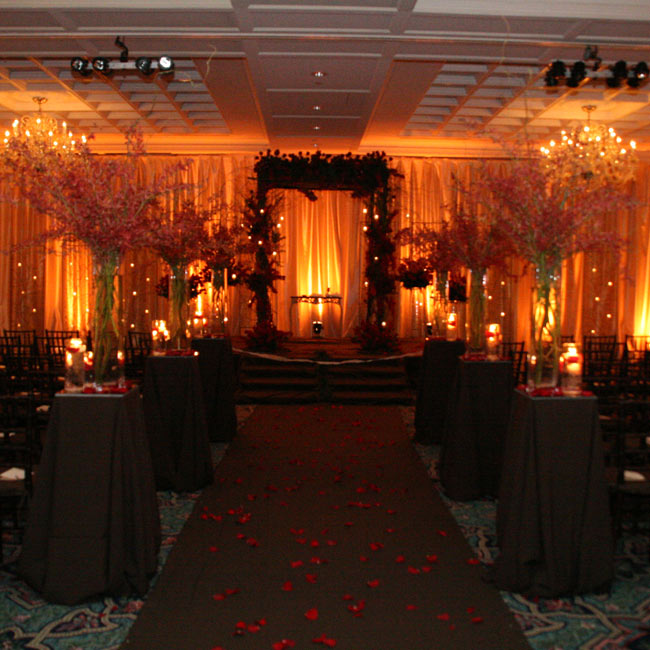 The huppah was decorated with an intertwining mix of branches and red flowers with hanging tea candles. Down the aisle, pedestals were draped in chocolate brown linen and topped with large glass vases filled with red orchids and shorter vases filled with rose petals and candles. The lighting was romantic and dim to reflect the warm and inviting moo ...