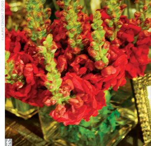 The centerpieces featured monochromatic bunches of red flowers in various-sized square vases.