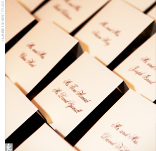 Guests were escorted to their tables with small ecru envelopes where each guest's name was written in chocolate brown. The cards were displayed on an antique wood and marble table in the cocktail area next to an ivory flower arrangement.
