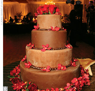 Guests devoured a four-tiered vanilla and chocolate cake that was filled with raspberry and chocolate mousse, covered in a rich, chocolate brown fondant, and adorned with red roses and orchids.