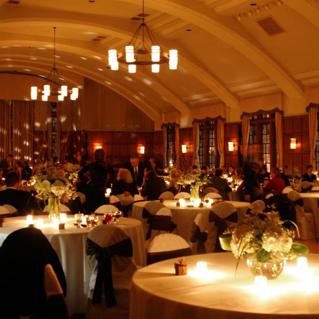 The ballroom at the Michigan League had a domed ivory ceiling, wood floors, wood paneling, and oversized chandeliers that created a warm, vintage feel. Each of the tables was draped in floor-length ivory linen, with matching ivory chair covers finished off in chocolate satin bows. The tables were adorned with favors of chocolate boxes filled with J ...