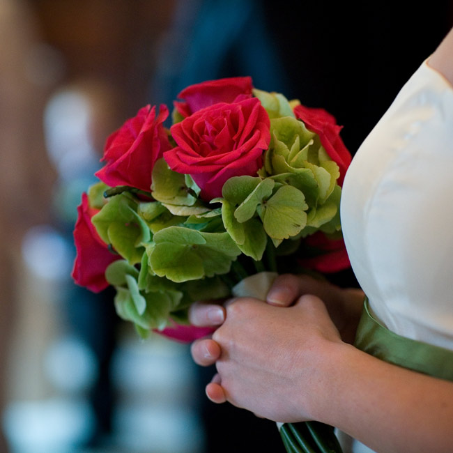 The bridesmaids walked down the aisle with bouquets of magenta roses mixed with green hydrangeas.