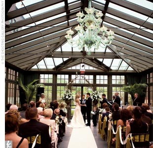 The ceremony was performed in the glass conservatory of the hotel. Amy and Kevin were surrounded by a lush garden and high trees with views of the elegant hotel peeking through on each side. Mahogany chiavari chairs, decorated with citron chair ties, were brought in for both the ceremony and the reception. The center aisle was draped with an ivory  ...