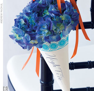 Guide guests to their table assignments using navy blue chairs as anchors. Turn nautical-themed flags into petal catchers and hang them with bright tangerine ribbon, and  for an extra burst of color, fill each table's marker with deep blue hydrangeas.Go behind the scenes of this photo shoot