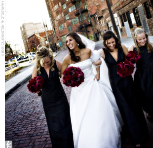 Danielles two bridesmaids wore black, silk shantung, V-neck dresses with Empire waists. The back featured a tie sash with a cutaway. The junior bridesmaid wore an A-line dress with spaghetti straps and an inset sash at the waist. Their bouquets of burgundy peonies and Black Magic roses popped against the dresses.