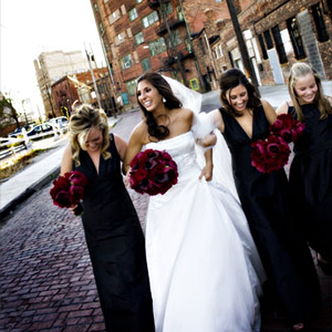 Danielle's two bridesmaids wore black, silk shantung, V-neck dresses with Empire waists. The back featured a tie sash with a cutaway. The junior bridesmaid wore an A-line dress with spaghetti straps and an inset sash at the waist. Their bouquets of burgundy peonies and Black Magic roses popped against the dresses.