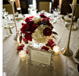 Small, square glass vases filled with Black Magic roses, burgundy dahlias, creamy white hydrangeas, and eucalyptus berries accented the center of each table.