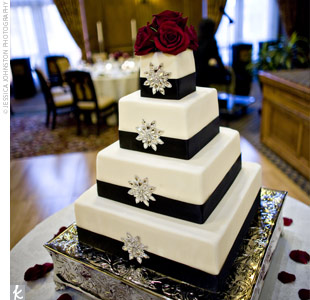 The four-tier square cake was covered in ivory fondant and decorated with black satin ribbon and jeweled appliques to mimic the brides gown. Guests indulged in layers of chocolate chiffon cake flavored with brandy, filled with a Kahlua mousse, and frosted with vanilla buttercream.