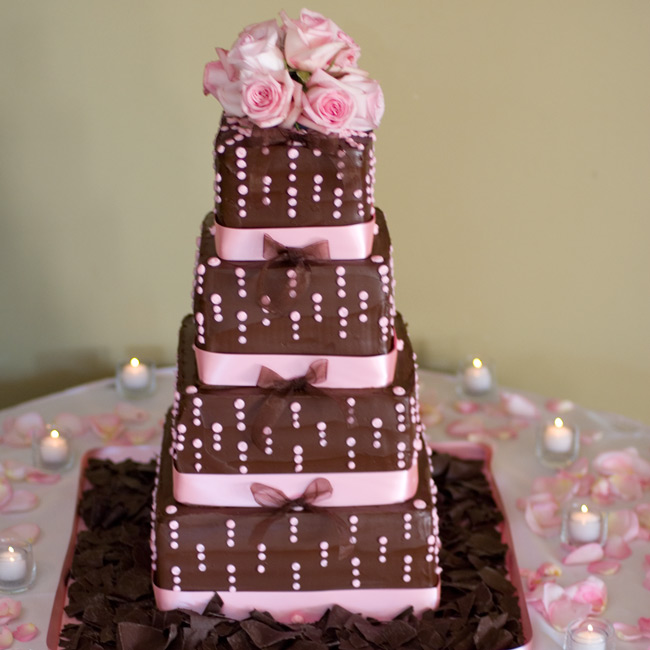 Guests indulged in a four-tiered, milk chocolate ganache-frosted cake decorated with a pink dot motif and pink ribbons. The alternating layers of white and chocolate cake were filled with strawberry mousse, Chantilly cream, and fresh strawberries. The confection was topped with a cluster of pink roses.