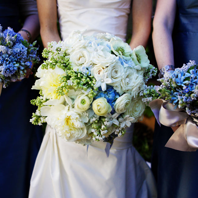 Cathy carried a pave-style bouquet with a mix of ivory peonies, roses, lilac, and stephanotis, mixed with blue hydrangeas. The stems were wrapped in light blue, satin ribbon. In contrast to the bride's bouquet, Cathy's bridesmaids carried similar garden-style bouquets in blue wrapped with oyster-hued ribbon.