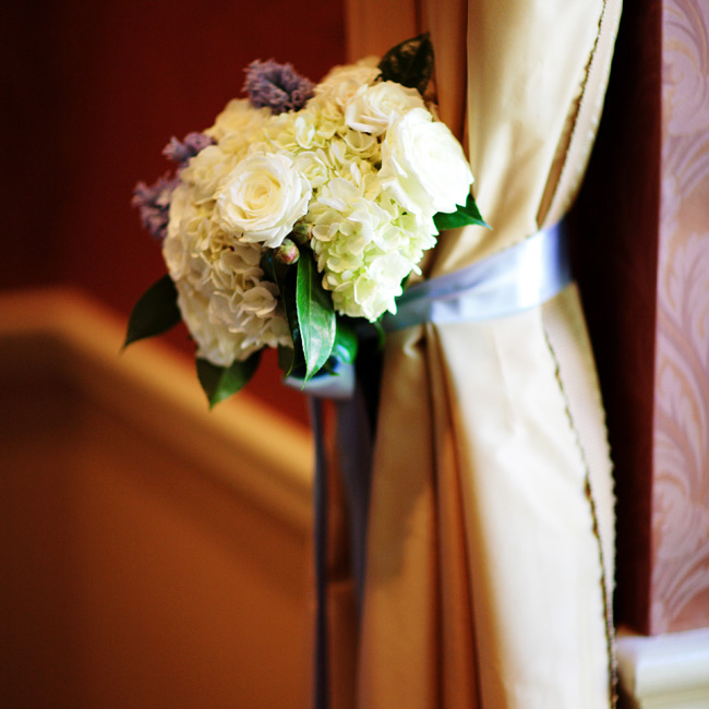 The curtains in the ceremony space were tied back with blue satin bows and tussie-mussies of ivory and blue hydrangeas, peonies, and muscari. The pew markers featured smaller bouquets of the same blooms.
