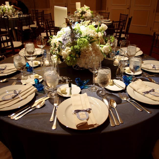 Cathy and Keith's dinner tables were covered with ivory shantung linens with blue organza overlays. Centerpieces of large bowls filled with peonies, hydrangeas, and light blue muscari were topped off with tiny wooden birds.