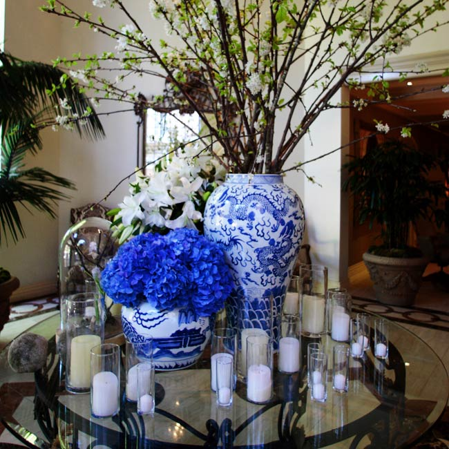 In the center of the reception space, two large tables were set up with large centerpieces featuring bird's nests set in their branches. Floating candles surrounded the arrangements.