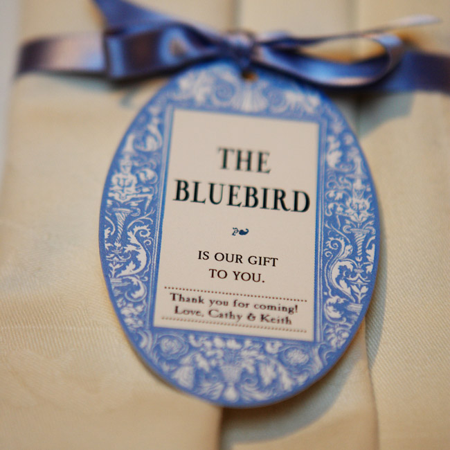 Guests found small, blue glass birds at each table setting. The napkins were tied with ribbons holding an egg-shaped tag threaded through letting guests know the birds were theirs to take home.