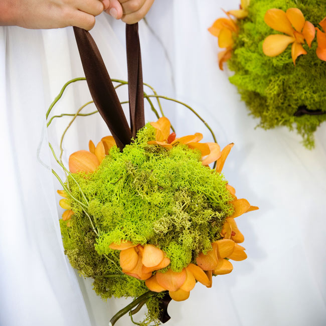 "All of the wedding flowers centered around Rebekah and Murrey's ""earthy glam"" theme, including the pomanders of moss and orchids carried by the flower girls. ""We wanted the flowers to look like wildflowers and be very natural looking,"" explains the bride."