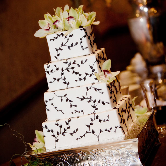 "Rebekah and Murrey's cake was a four-tier ivory cake accented with chocolate brown piping of branches and leaves for a ""vintage earthy look."" Fresh, green cymbidium orchids accented the confection."