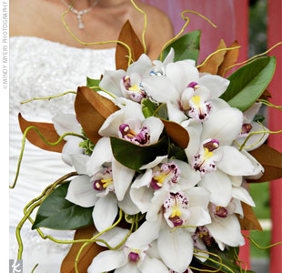 The bride carried a simple, exotic bouquet of white cymbidium orchids with a touch of magenta and yellow in the center and surrounded by green-and rust-colored magnolia leaves and twisted green willow. Nikki had the florist include a vintage silver brooch with light blue and white stones, which had belonged to her grandmother who passed away from b ...