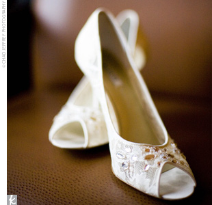 Jennifer wore ivory-beaded, peep-toe pumps to complement her ivory, tulle and organza, A-line, beaded lace gown.