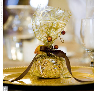 Half of the place settings were adorned with homemade chocolate favors, and the other half featured caramel apples, wrapped in clear and gold bags and tied off with ribbon and berries.