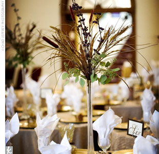 The couple's florist created half of the centerpieces using fall elements, including wheat stalks, cattails, berries, and greenery. The arrangements were set at the tables and surrounded with soft votive candles.