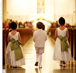 The flower girls wore sleeveless, satin, Empire-waist dresses in ivory. They also wore sashes custom made to match the sage green used throughout the wedding.