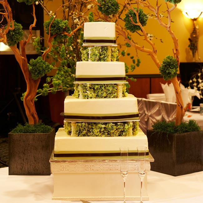 Ivy and Danny served their guests a four-tiered square cake decorated with bands of sage green and chocolate brown ribbon around each tier. Green hydrangeas sprouted from between the tiers. Manzanita trees adorned with balls of flower petals flanked the cake on either side.