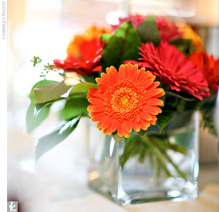 Multicolored gerbera daisies in square vases added a touch of color to the each table.