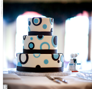 Sarah and Sam chose several flavors for their wedding cake: white cake with chocolate and raspberry filling and chocolate cake with white Russian filling. The confection was iced with buttercream and decorated with mod brown and blue circles.