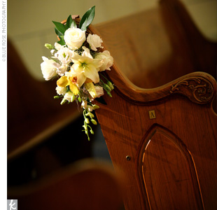 Hanging arrangements of white and gold orchids, white roses, and greenery hung from the aisle pews.