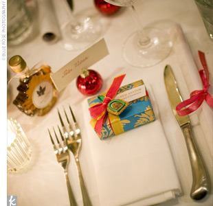 Brightly wrapped turquoise, red, and gold boxes were filled with chocolates and displayed at each place setting. In addition to chocolates, guests were given custom-printed calendars and a bottle of fresh maple syrup with custom labels to celebrate that their wedding fell on National Maple Syrup Day.