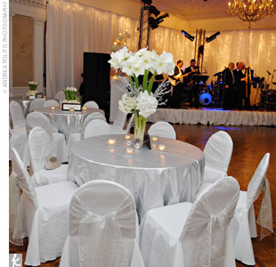 "Elizabeth and Jim worked with event designer Nelson Robinson to create a ""wow factor"" for the wedding. One major element was the stage behind their band, which was draped with white fabric, lights, and branches."