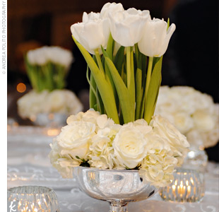Other tables at Elizabeth and Jim's reception boasted low, lush arrangements of white tulips sprouting from silver urns filled with white roses and hydrangeas. Mirrored ornaments and silver balls also added to the lush look of the tables.