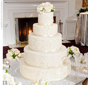 The wedding cakes were displayed in the entryway so that guests passed by them on their way into the reception. The bride's cake was a round, ivory cake with crystals rimming each tier.
