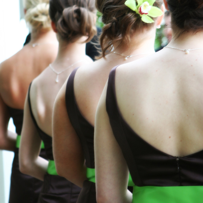 "Julie's four bridesmaids wore chocolate brown tea-length gowns by Jim Hjelm. ""The dresses were accented with a bright lime sash to bring a springy feel to the chocolate satin,"" the bride says."