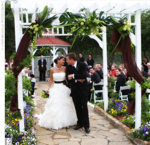 Julie and Eric said I do beneath a gazebo with their guests seated around them in white garden chairs. An archway leading up to the gazebo was adorned with tropical leaves, green flowers, and chocolate tulle. We were so lucky it stopped raining just long enough for us to have this lush tropical atmosphere and exchange vows in the fresh air, Jul ...