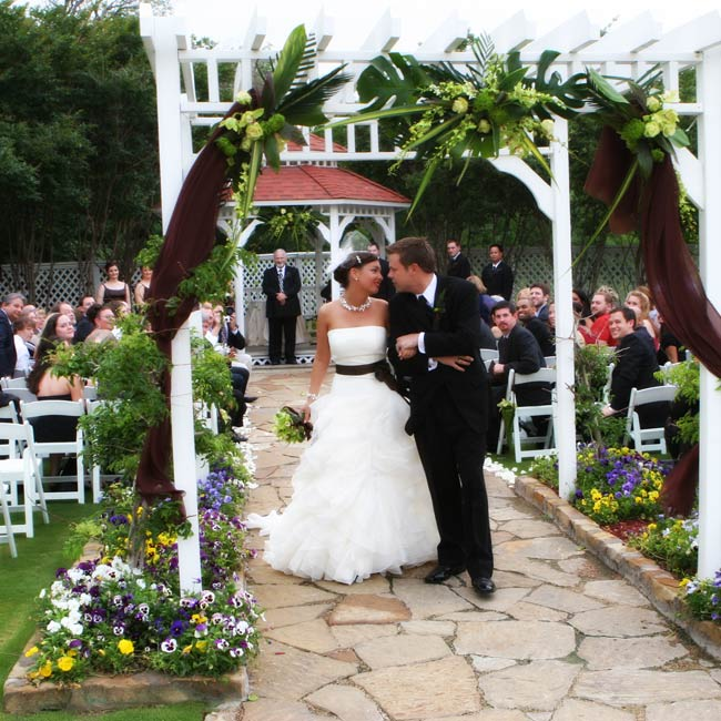 "Julie and Eric said ""I do"" beneath a gazebo with their guests seated around them in white garden chairs. An archway leading up to the gazebo was adorned with tropical leaves, green flowers, and chocolate tulle. ""We were so lucky it stopped raining just long enough for us to have this lush tropical atmosphere and exchange vows in the fresh air,"" Jul ..."