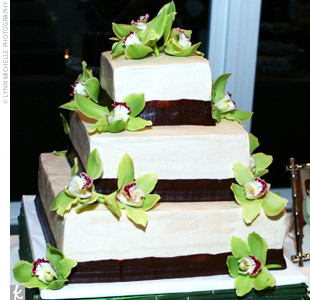 "Julie and Eric cut a three-tiered square cake frosted in ivory with a ribbon of chocolate around each tier. The base the cake stood on was covered in bamboo, ""giving it a modern feel,"" the bride says."