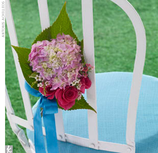 A simple white garden ceremony chair ties in the garden party theme perfectly when dressed up with a blue chair cushion and fresh hydrangeas and roses.