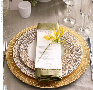 A yellow flower adds a lively touch to an ornate gold place setting.