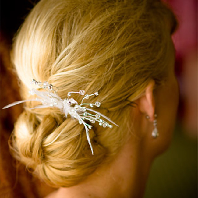 Lauren's hair was pulled into a loose, low bun adorned with a Malis-Henderson comb embellished with crystals and ivory feathers.