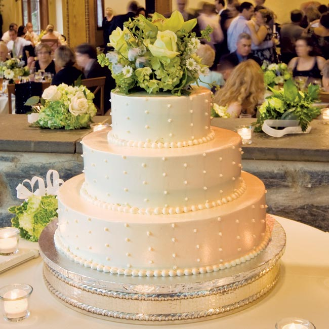 Lauren and Gilles' guests enjoyed a three-tier ivory cake adorned with Swiss dots and an arrangement of fresh green flowers on the top tier.