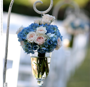 Shepherd's hooks with glass vases filled with blue hydrangeas and white roses lined the aisle. A gazebo was decorated with southern smilax, blue delphiniums, blue hydrangeas, blue scabiosas, and white roses.