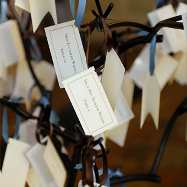 Abbey and John's escort cards hung from ribbons at a table near the entrance to the reception. The table also featured a large urn filled with blue and white hydrangeas and scabiosas, white roses, and blue delphiniums.