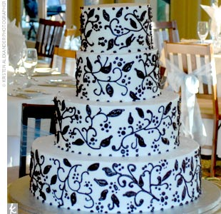 Abbey and John's four-tier white cake with raspberry filling featured buttercream icing with a chocolate brown ivy design.