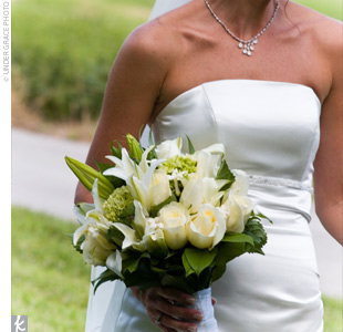 Staci walked down the aisle holding a white textured bouquet surrounded by greenery and tied off with a white ribbon.
