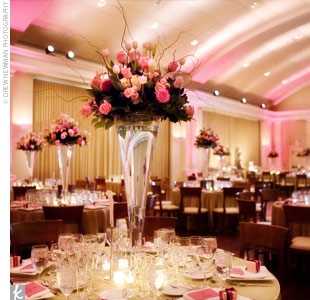 Pink and amber lighting and tall centerpieces set the stage at Alison and Chris' reception. Each place setting was set with a square charger and a cranberry-hued menu card.
