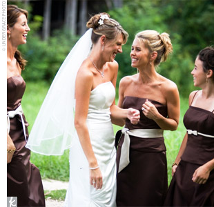 Staci's bridesmaids wore chocolate brown, satin dresses with champagne-colored sashes. They held bouquets made of cymbidium orchids and orange accent flowers.
