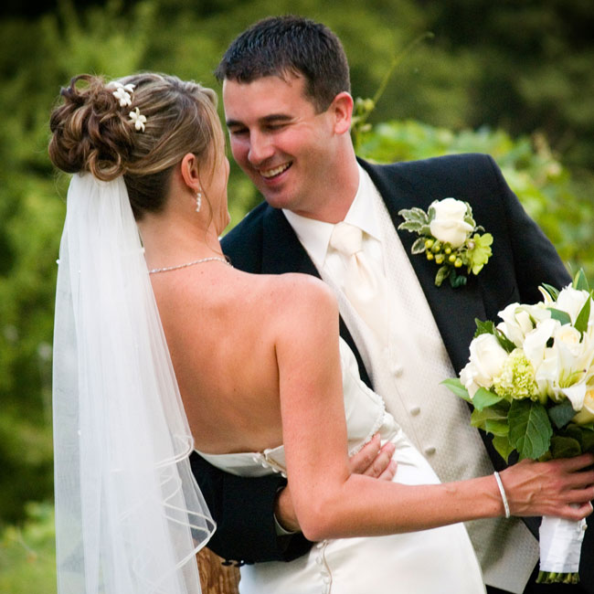 For her hairstyle, Staci wanted to keep the look as natural as possible. Her simple veil cascaded from beneath her updo, and her stylist slipped white stephanotis blooms into her hair for a pretty accent.
