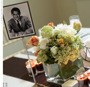 Alison and Joe didn't want to take away from their reception room's already elegant decor, so they opted for centerpieces of low, square vases filled with orange and ivory ranunculuses and parrot tulips. The couple showcased their wedding day theme -- old Hollywood glamour -- with table numbers that included black-and-white photos of Hollywood acto ...