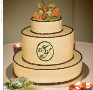 Alison and Joe's three-tiered cake was covered in ivory buttercream and piped with chocolate brown pearls around each tier. The thicker middle tier was accented with a chocolate plaque with the couple's monogram.